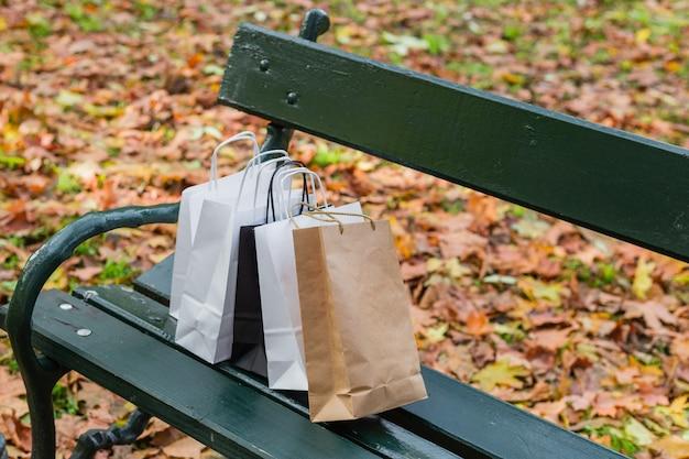 Boodschappentassen op een groene bank, kopieer ruimte. winkelconcept. mockup, blanco papieren zak boven de bank