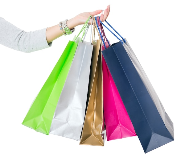 Boodschappentassen. vrouwelijke hand met kleurrijke boodschappentassen op wit.