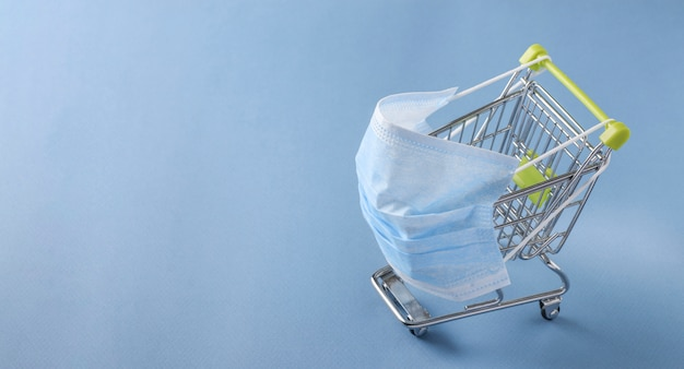 Boodschappentrolley in beschermend masker, concept van gevaren van winkelen tijdens de pandemie van het coronavirus covid-19, ruimte kopiëren