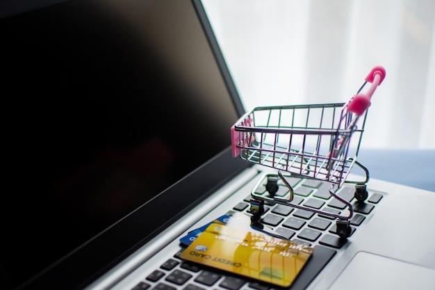 Boodschappenwagentje en creditcard op computer, winkelend online concept.