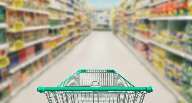 Boodschappenwagentje in supermarkt en de vage bokeh achtergrond van de fotoopslag