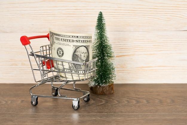 Boodschappenwagentje met dollarsbankbiljetten en kerstboom over houten achtergrond