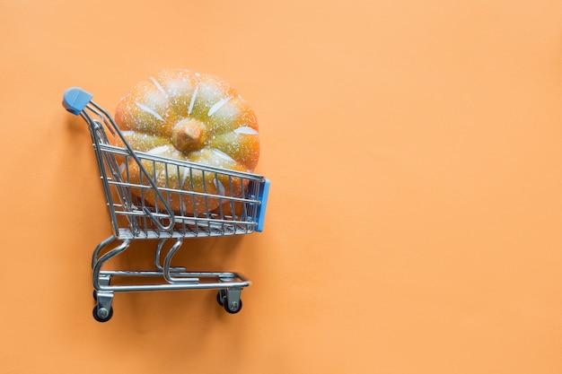 Boodschappenwagentje met pompoen op sinaasappel. halloween winkelen en verkoop. plat lag, bovenaanzicht.