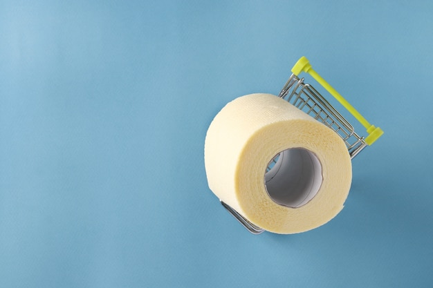 Boodschappenwagentje met rol zacht toiletpapier op blauwe achtergrond, covid-19 pandemie, verhoogde onverwachte vraag, kopieerruimte
