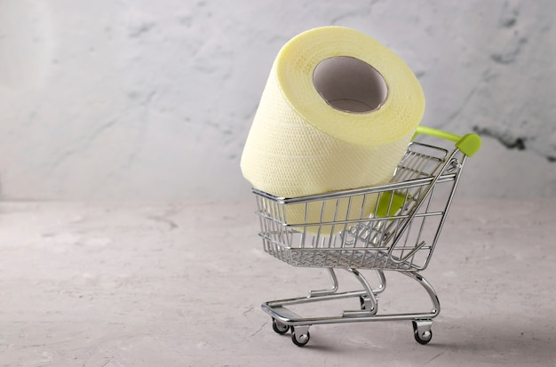 Boodschappenwagentje met rol zacht toiletpapier op grijze achtergrond, covid-19 pandemie, toegenomen onverwachte vraag, kopieerruimte