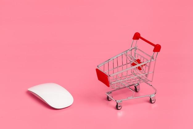 Boodschappenwagentje of supermarktkarretje op roze achtergrond