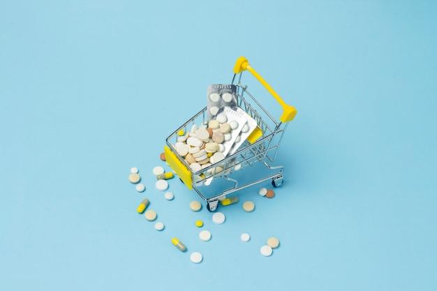 Boodschappenwagentje van het supermarkthoogtepunt van pillen op een blauwe achtergrond. aankopen van medische preparaten, aankopen op internet. plat lag, bovenaanzicht.
