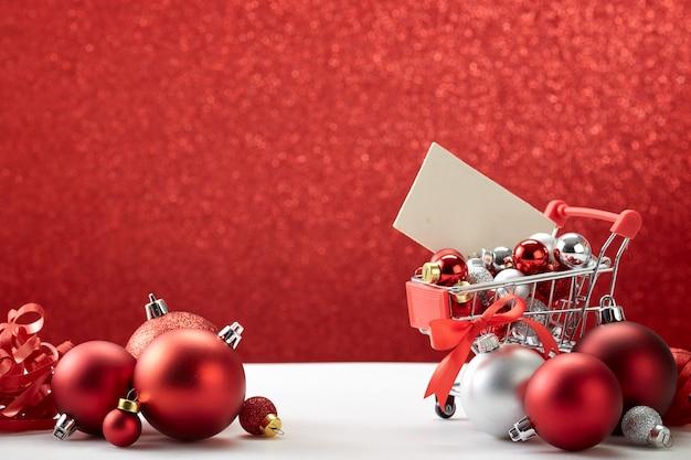 Boodschappenwagentjehoogtepunt van kerstmisornamenten op rode achtergrond