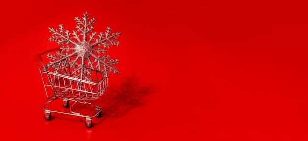 Boodschappenwagentjestuk speelgoed met kerstmisspeelgoed en rode muur. kopieer ruimte. kortingen, verkoop. kerst- en nieuwjaarsuitverkoop.