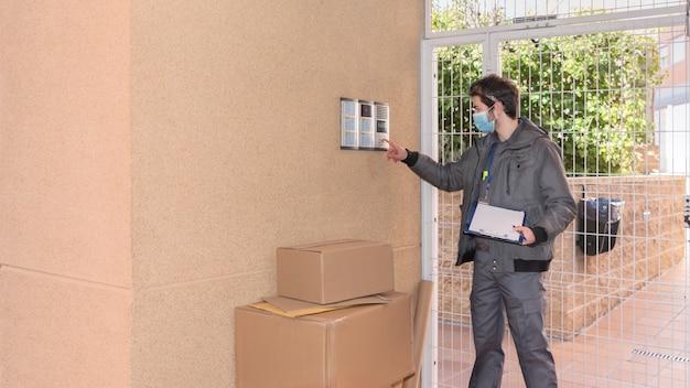 Boodschapper met masker bezorgt pakketten aan de deuropening naast de deurwachter