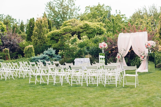 Boog en stoelen voor de huwelijksceremonie, versierd met stoffen en bloemige composities