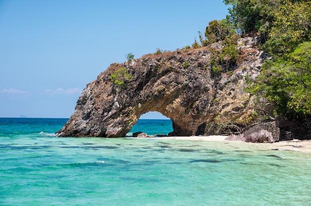 Boog natuurlijke rots op turkooise overzees en het strand