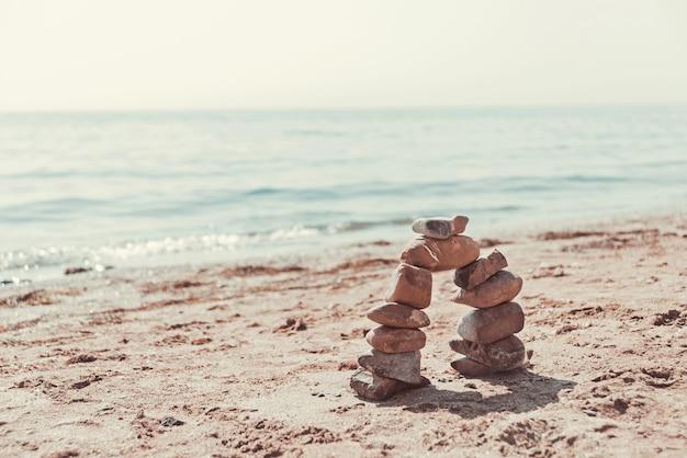 Boog van stenen op het strand van de zeezomer