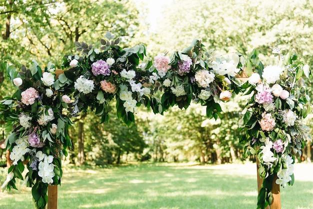 Boog voor de huwelijksceremonie. boog, versierd met prachtige verse bloemen en stof. registratie op de plaats van huwelijk.
