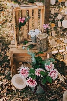 Boog voor de huwelijksceremonie van jute en houten logboeken in dennenbos