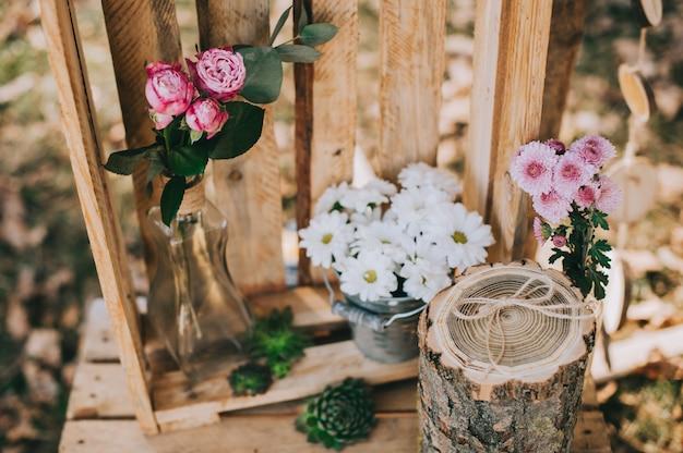 Boog voor de huwelijksceremonie van jute en houten logs in dennenbos