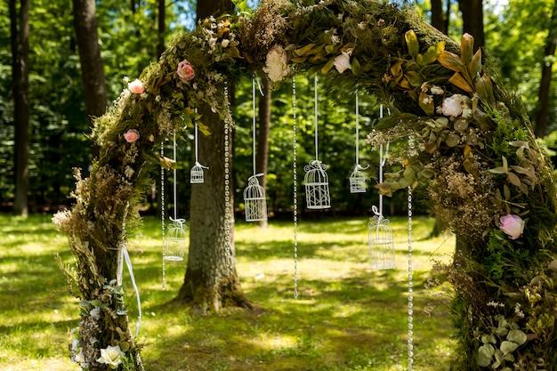 Boog voor de huwelijksceremonie. versierd met bloemen en groen. ligt in een dennenbos. net getrouwd.