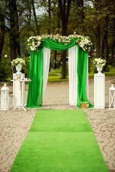 Boog voor de huwelijksceremonie, versierd met groene en witte doek en bloemen buitenshuis.