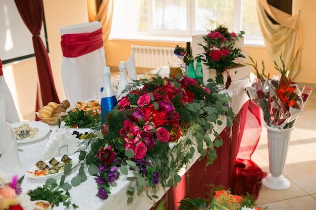 Boog voor de huwelijksceremonie, versierd met stoffen bloemen en groen, bevindt zich in een dennenbos