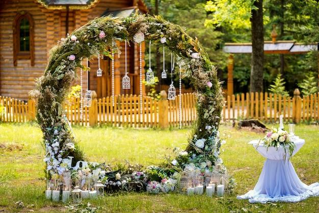 Boog voor de huwelijksceremonie. versierd met stoffen bloemen en groen. ligt in een dennenbos.
