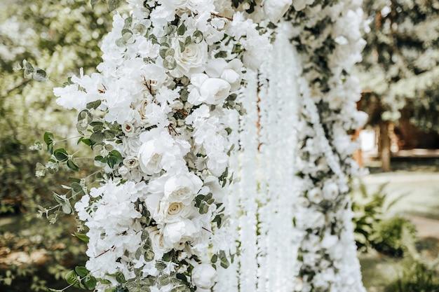 Boogdecor met witte bloemen voor een huwelijksceremonie in de natuur