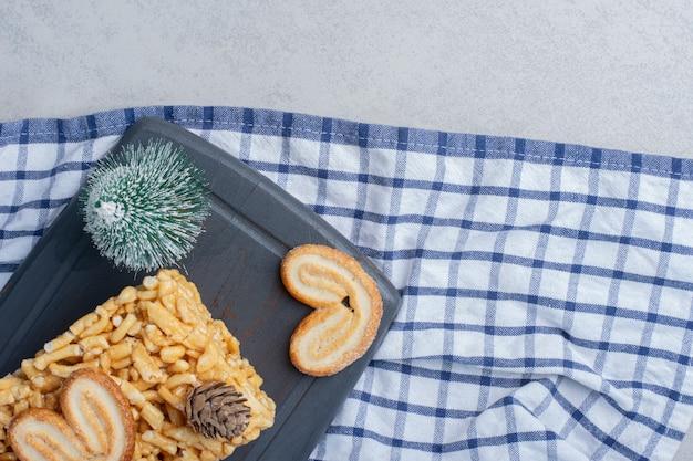 Boom, beeldje, koektaart en schilferige koekjes op een bord op marmeren oppervlak