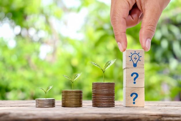 Boom groeit op geld en investeerder hand met houten blok met gloeilamp icoon geld groeiend concept en het kopen van een huis of condo