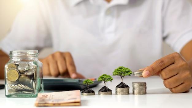Boom groeit op stapel geld en zakenman die munten in de hand houdt idee om de winst uit bedrijfsinvesteringen te maximaliseren.