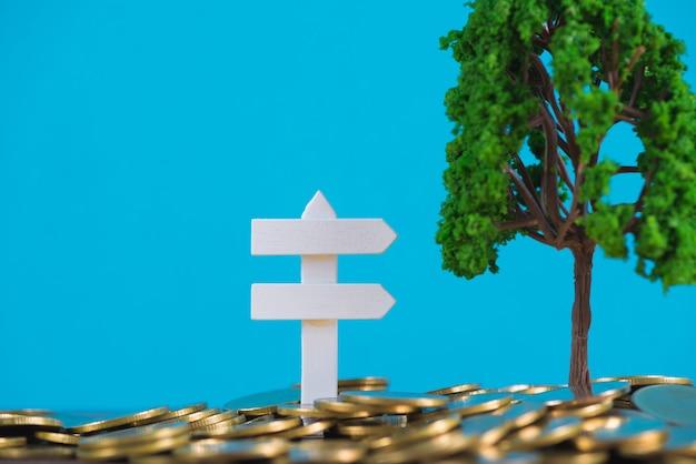 Boom het groeien op stapel van gouden muntstukken en wit houten raadsteken,