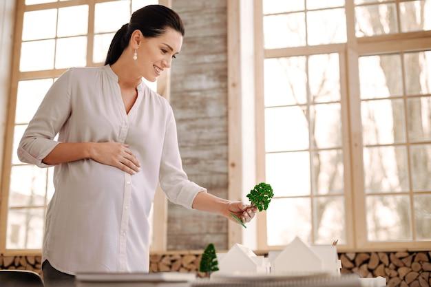 Boom hier. blije bekwame zwangere ontwerper die boommodel houdt terwijl grijnzend en hand op buik legt