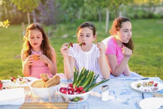 Boom kleine schattige meisjes zitten bij de tafel in de natuur en lunchen.