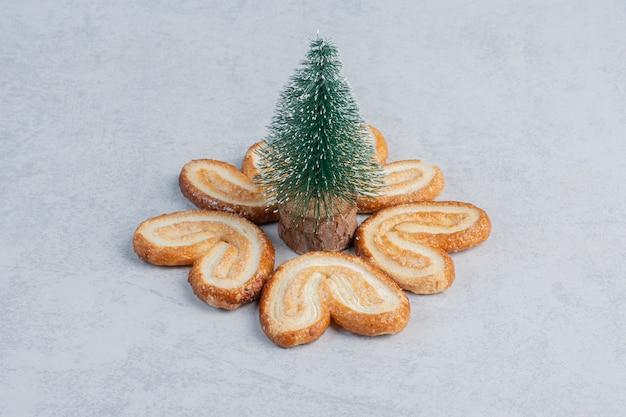 Boombeeldje omringd met schilferige koekjes op marmeren oppervlak