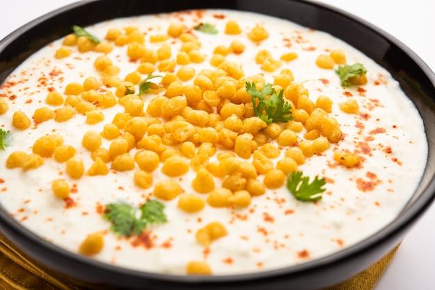 Boondi raita is een noord-indiase bijgerechtvariëteit gemaakt met gekruide yoghurt en boondi of knapperige gebakken grammeelballen Premium Foto