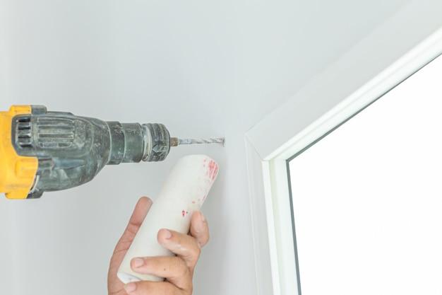 Boor de boor aan de vensterrand om het gordijn te monteren