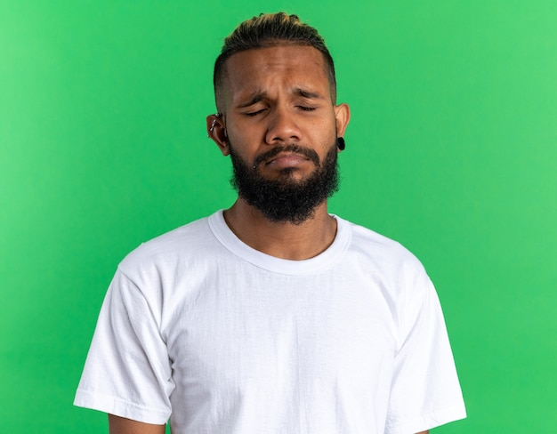 Boos afro-amerikaanse jongeman in wit t-shirt met droevige uitdrukking tuitende lippen met gesloten ogen