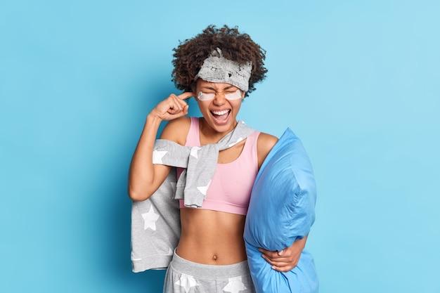 Boos afro-amerikaanse vrouw roept met gesloten oor, geïrriteerd door storend hard geluid, kan niet in slaap vallen vanwege muziek gekleed in slaappak houdt kussen onder de arm geïsoleerd op blauwe muur