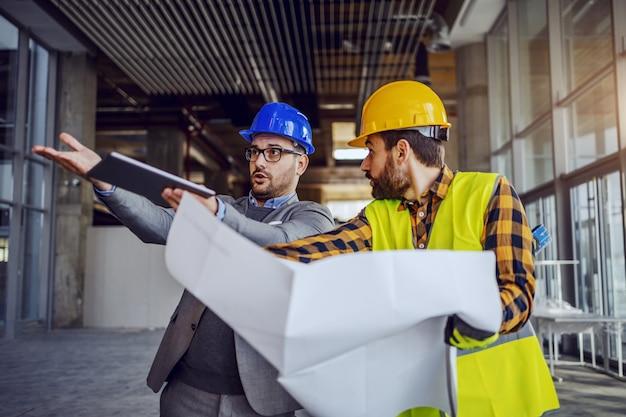 Boos architect ruzie met bouwvakker en toont hem zijn fout. arbeider die blauwdrukken houdt en zich verdedigt. bouwen in bouwproces interieur.