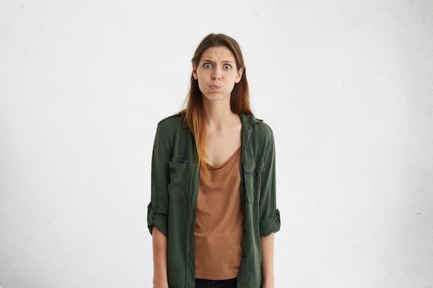 Boos beledigde brunette vrouw kijkt met grote ogen en wangen blazen, geïrriteerd