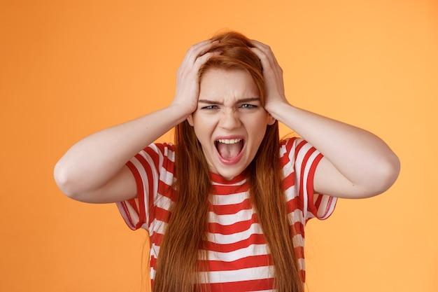 Boos beu roodharige vrouwelijke tiener geërgerd breken grijp het hoofd schreeuwen hatelijk ontstemd depressief...