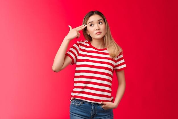 Boos blond aziatisch meisje draagt gestreept t-shirt jeans sterven verveling zuchtend kijk omhoog houd vinger geweer pisto...