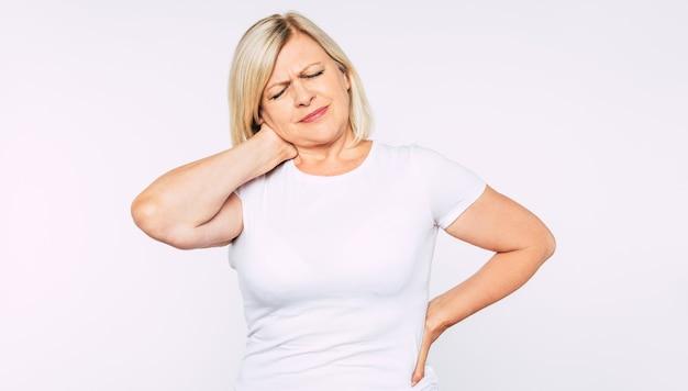 Boos blonde senior vrouw met sterke rug- en nekpijn