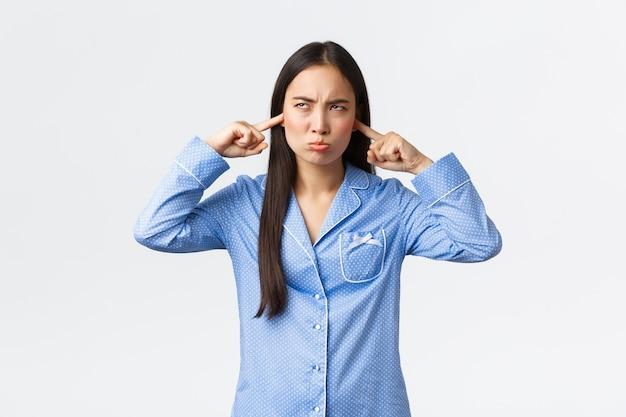 Boos chagrijnig aziatisch meisje in blauwe pyjama klagen luide buren in de slaapzaal van de universiteit, kijken gehinderd en ontevreden op, sloot de oren van vreselijk lawaai, staande witte achtergrond.