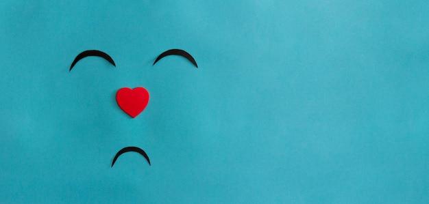 Boos concept. smileygezicht op blauwe achtergrond met hartneus. ruimte kopiëren.