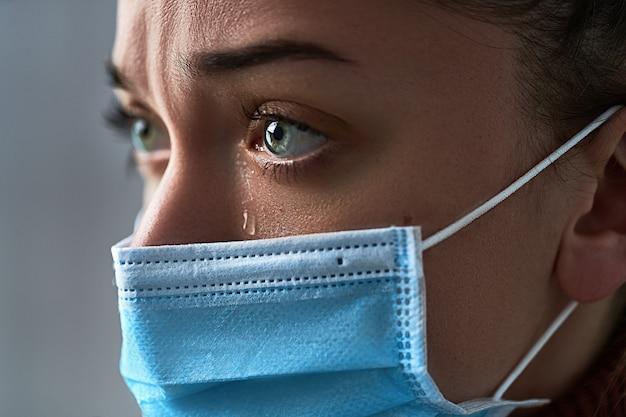 Boos depressief huilende trieste vrouw in beschermend gezichtsmasker met tranen ogen close-up tijdens ziekte