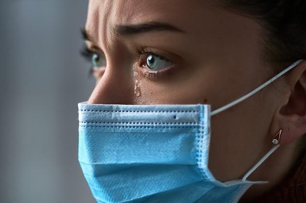 Boos depressief melancholische triest huilende vrouw in beschermend gezichtsmasker met tranen ogen tijdens ernstige ziekte