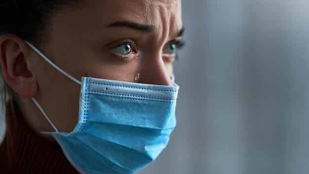 Boos depressief triest bedroefd huilende vrouw in beschermend masker met tranen ogen tijdens ziekte