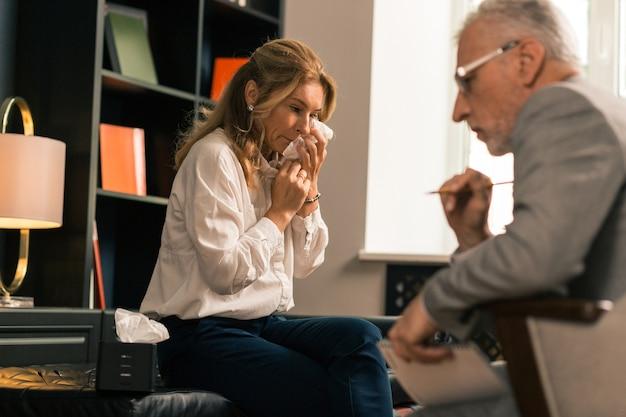 Boos depressieve blonde vrouw huilen terwijl ze klaagt over haar psychische problemen bij haar psycholoog