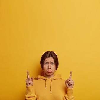 Boos, depressieve europese vrouw wacht op uitleg, kijkt droevig, wijst met de vingers omhoog, toont iets onaangenaams naar boven, tuit lippen, draagt hoodie, modellen over gele muur