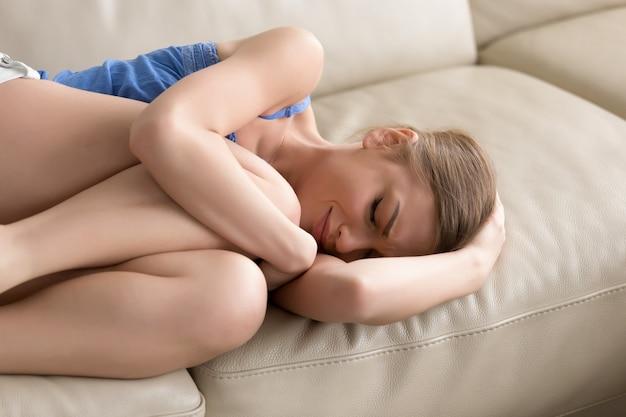 Boos depressieve tiener liggend op de bank, huilen omarmen haar knieën