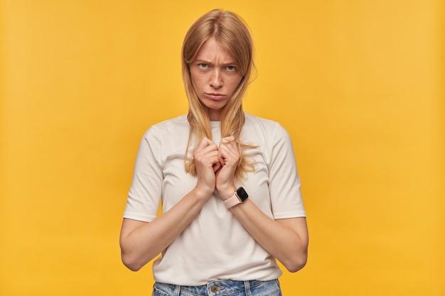 Boos depressieve vrouw met sproeten in witte t-shirt ziet er beledigd uit en houdt haar haar op geel